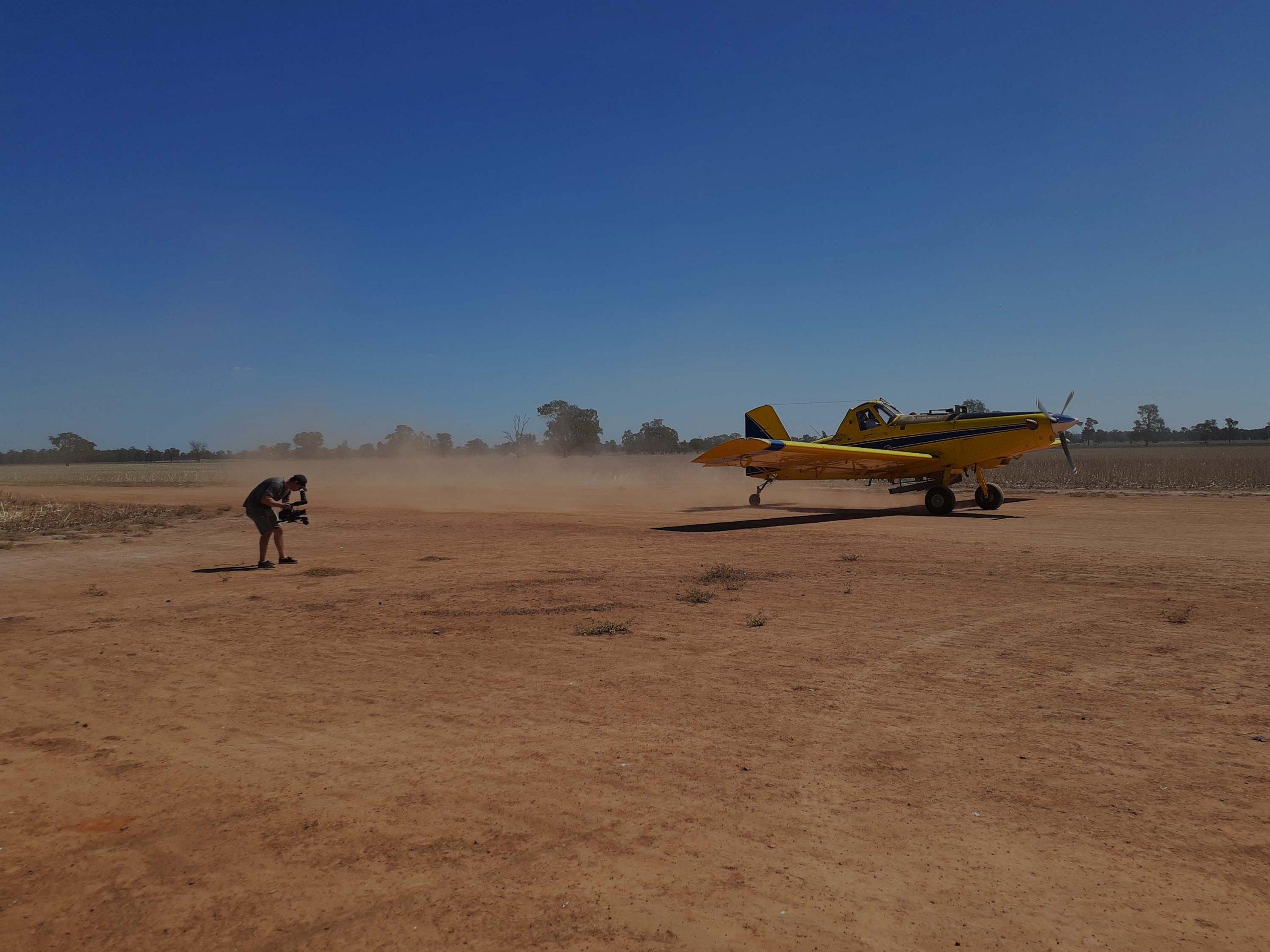 Videographer shooting small plane taking off